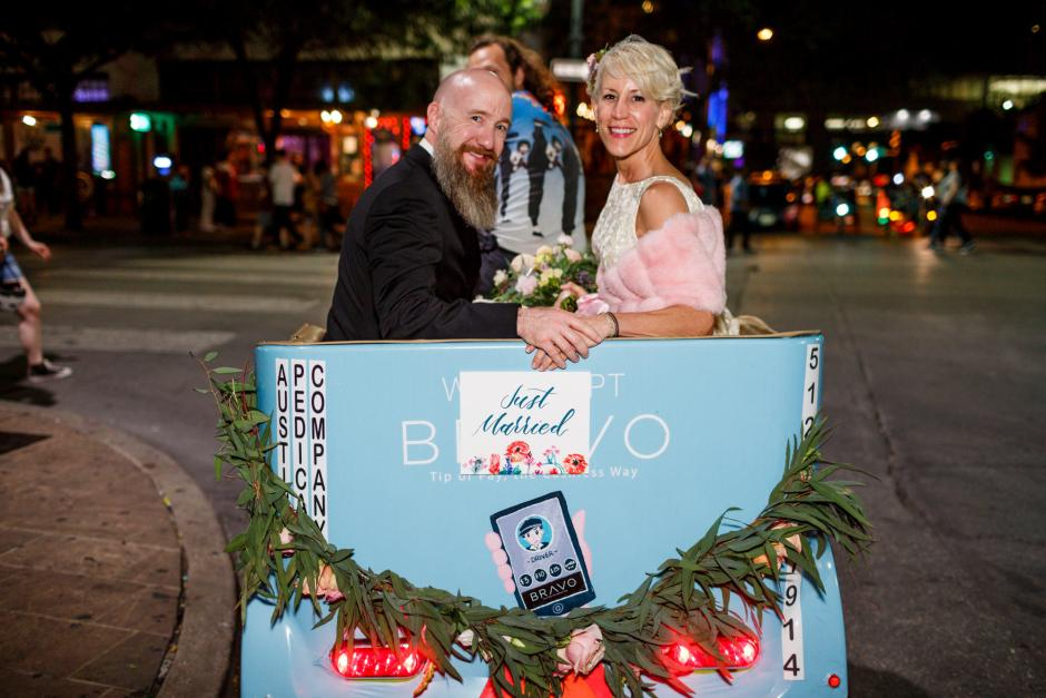 Mike and Kathie exit their Palm Door on Sixth Wedding reception on a rickshaw in downtown Austin.