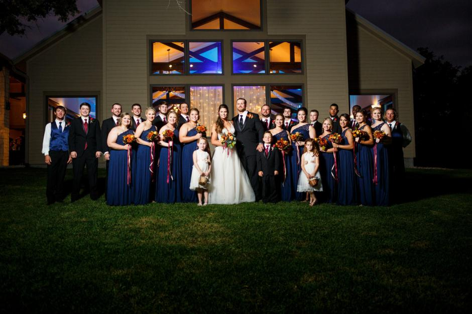 Formal portraits of entire large wedding party in front of the main ball room at Cathedral Oaks.