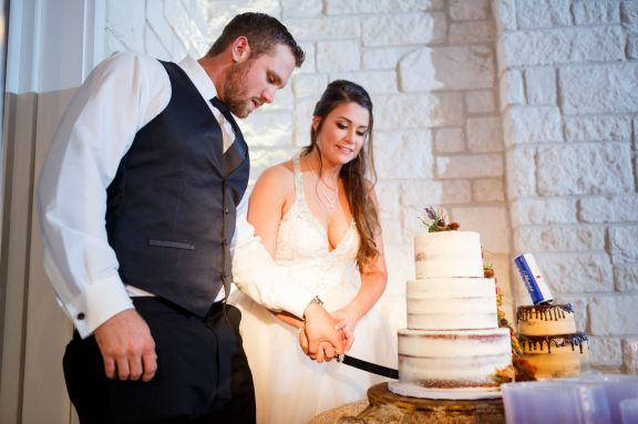 Bride and groom cut the cake at their Cathedral Oaks wedding reception.