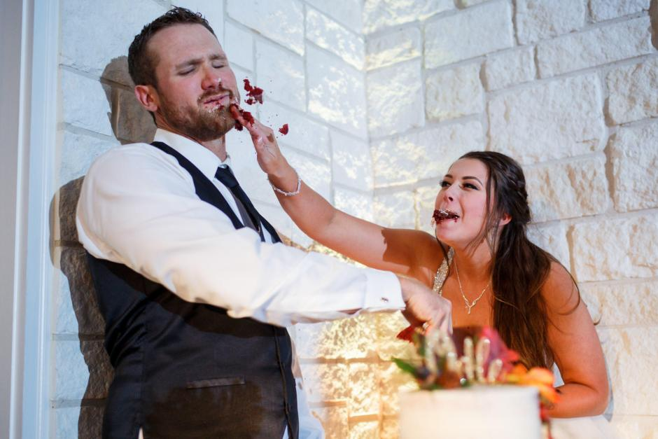 Bride smashes cake on the groom's face during her wedding reception at Cathedral Oaks in Belton, Texas.
