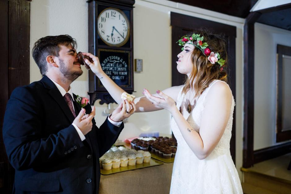 Meagan smashes a cupcake on Austin's face at their old fashion wedding in Denhawken, Tx near San Antonio.