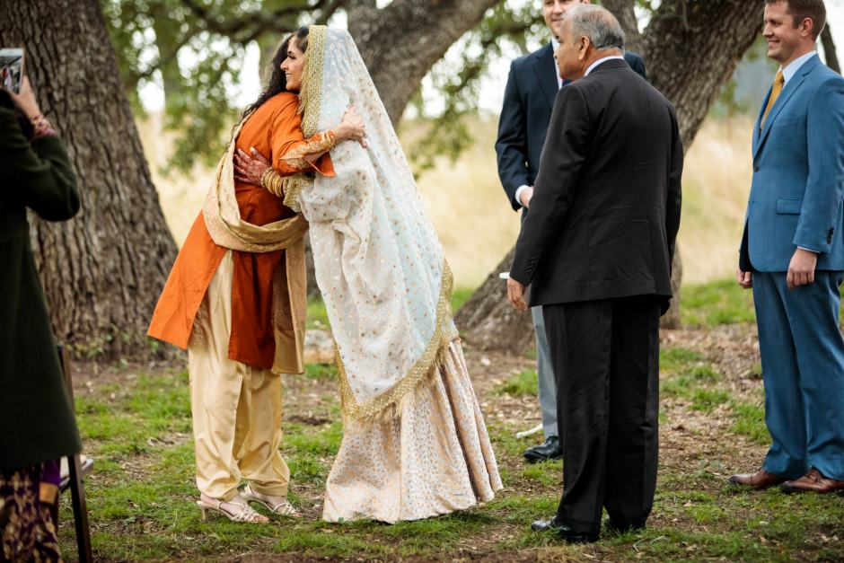 Bride hugs her mom during her outdoor wedding ceremony under large oak trees - Heart of Texas Ranch Wedding in Marble Falls Texas - Indian-Christian Fusion Wedding