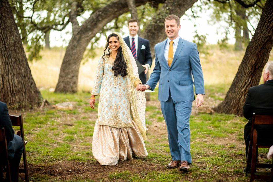 Smiling bride and groom walk down the isle after their Heart of Texas Ranch wedding in Marble Falls Texas under large oak trees- Indian-Christian Fusion Wedding