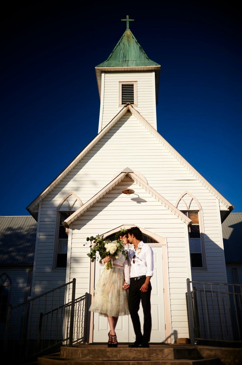 Austin Wedding Style - Styled Wedding Shoot - Couple kisses in front of a old country church outside Austin