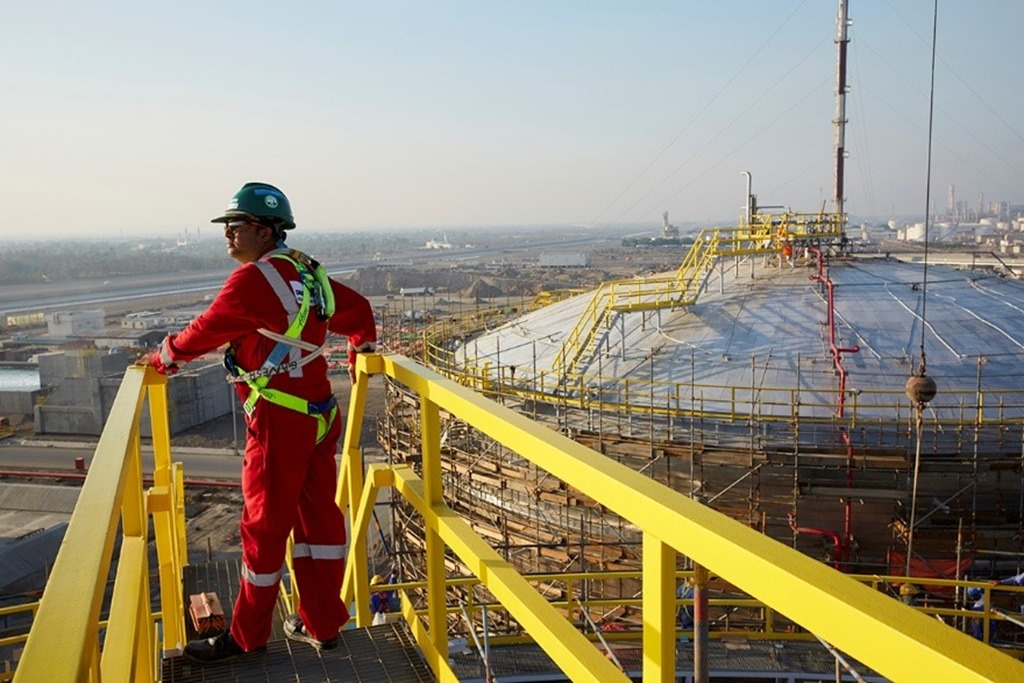 A Petrofac worker standing on metal scaffolding at a work site.