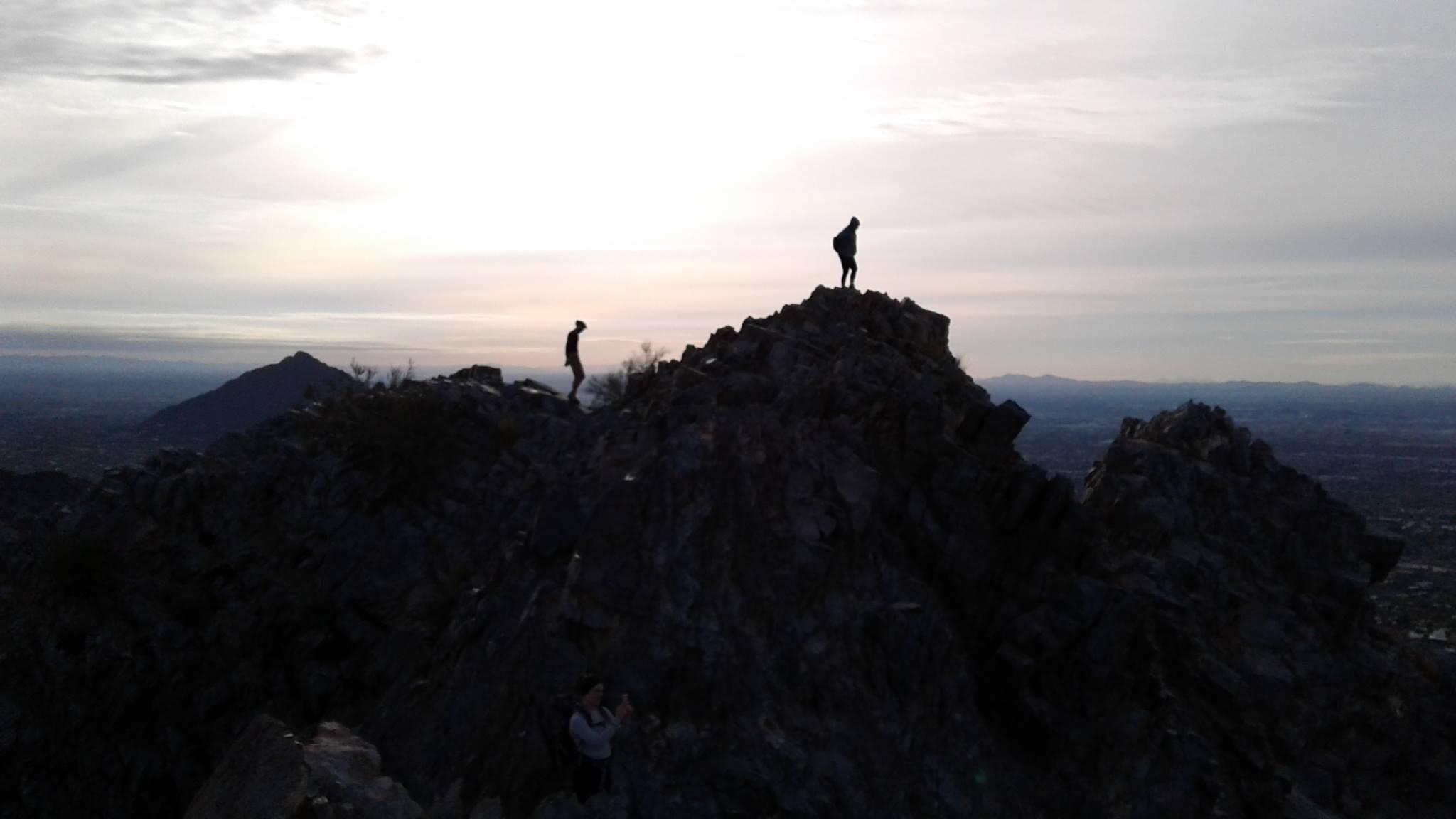Silhouette of hikers on mountain peak