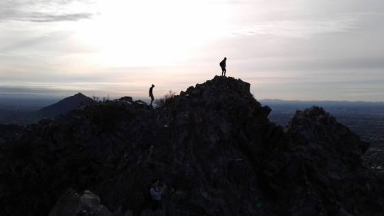 Silhouette of hikers on mountain peak