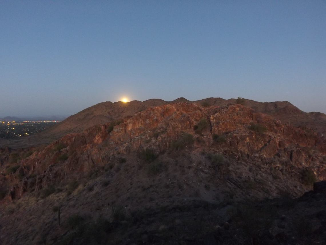 full moon rising from behind rocky hill