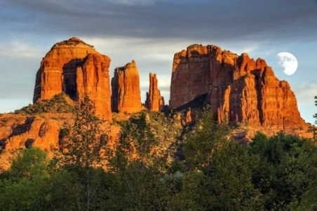 Moon rises behind sun-drenched red rock formations in Sedona, AZ
