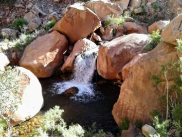 Large red rock boulders with waterfall running through them