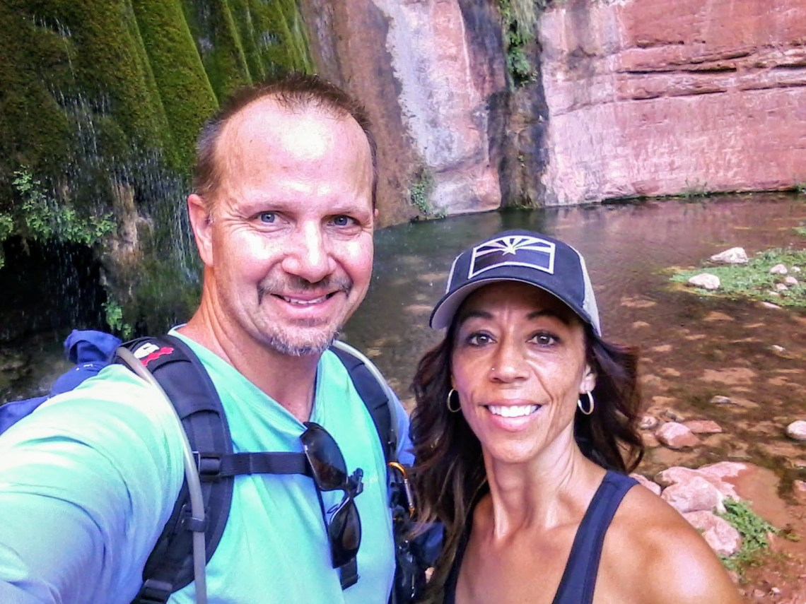 Selfie of couple in front of waterfall