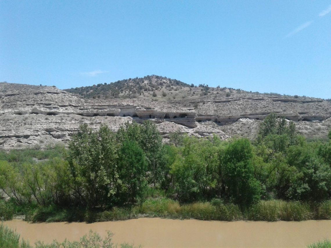 Cave dwellings in the distance with muddy river and lush trees in the foreground