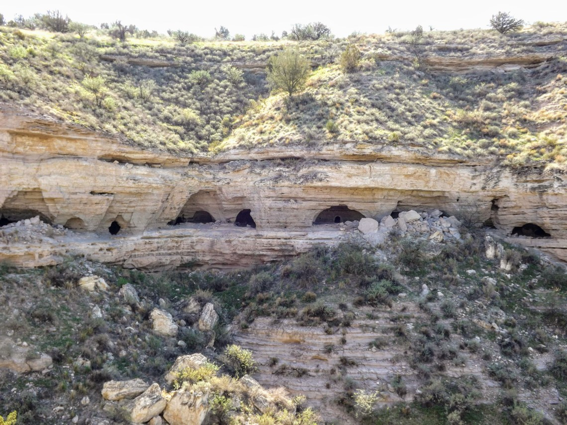Wide shot of caves dug into the wall of a canyon