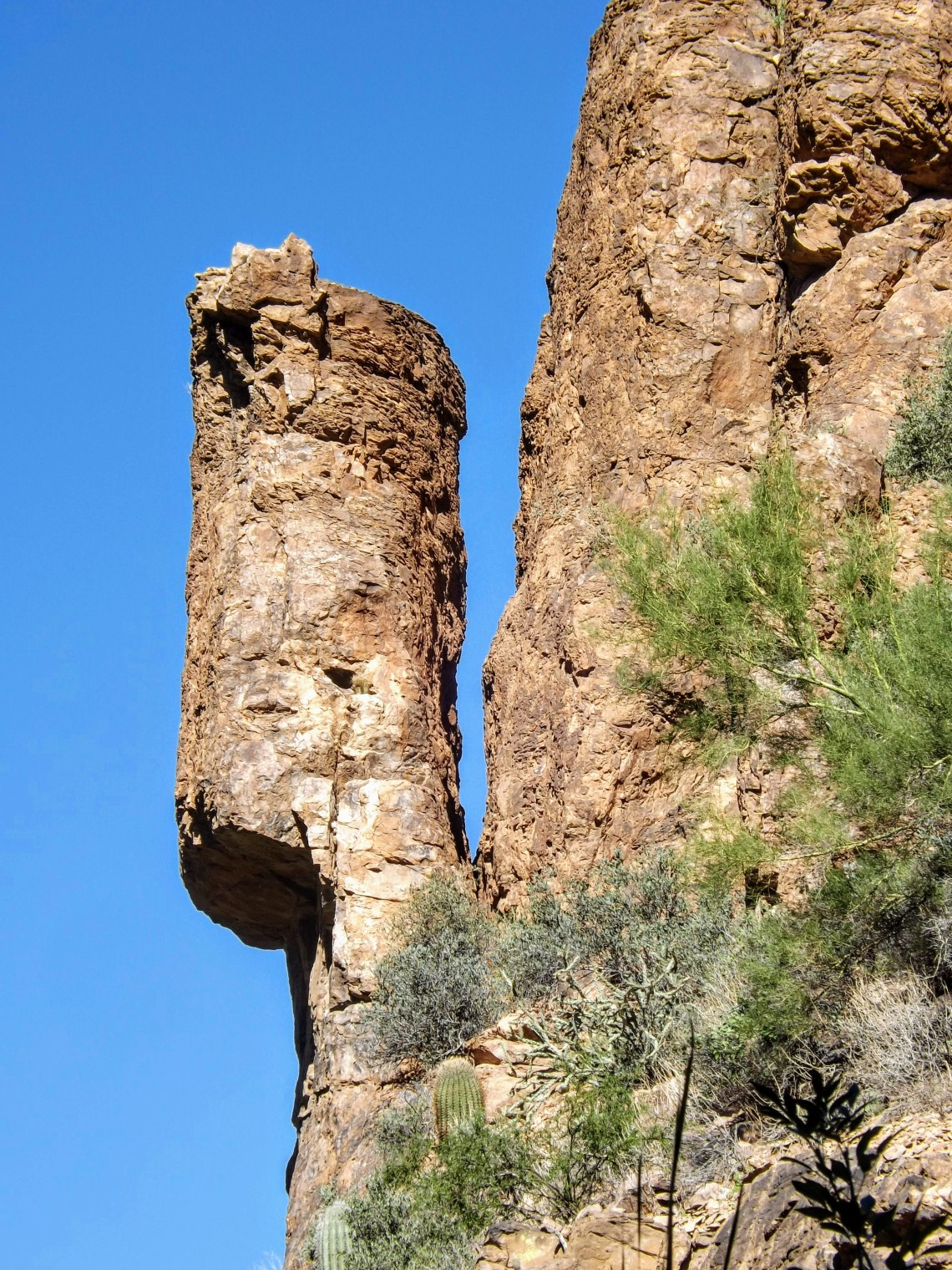 Large totem-like rock separated from rock cliff