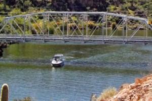 Motorboat passes under bridge as it exits cove