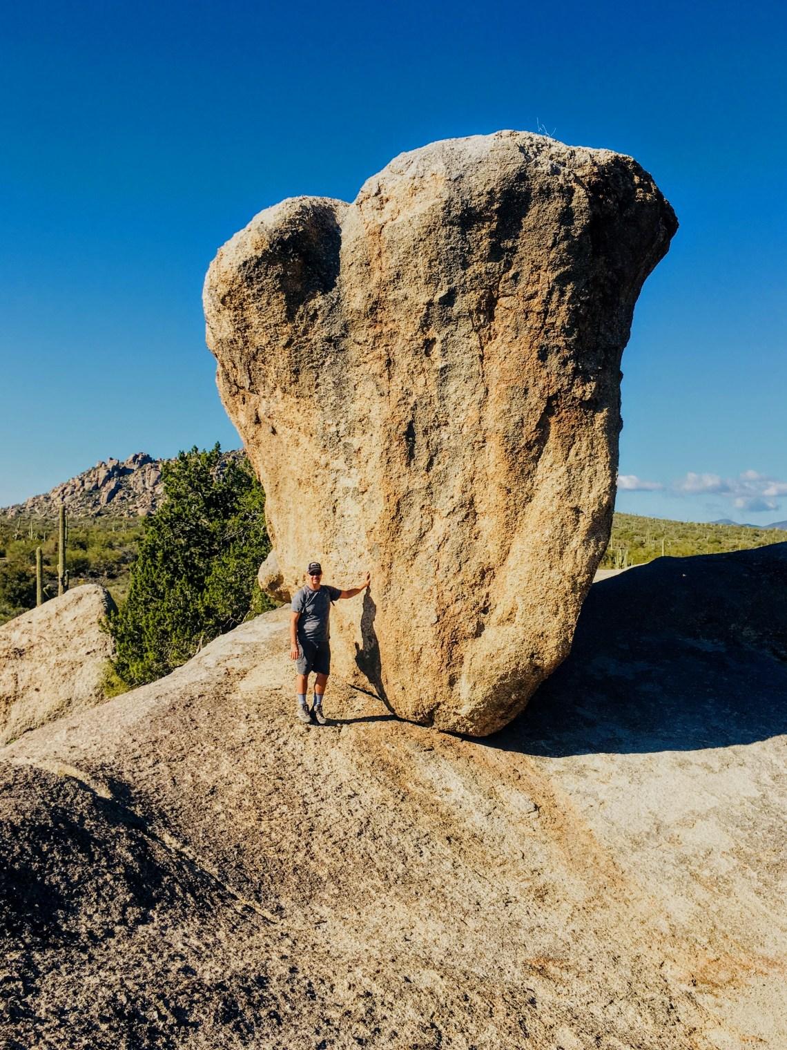 man standing at base of large balanced rock