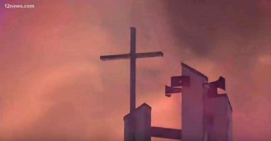Cross stands tall with flame glow all around