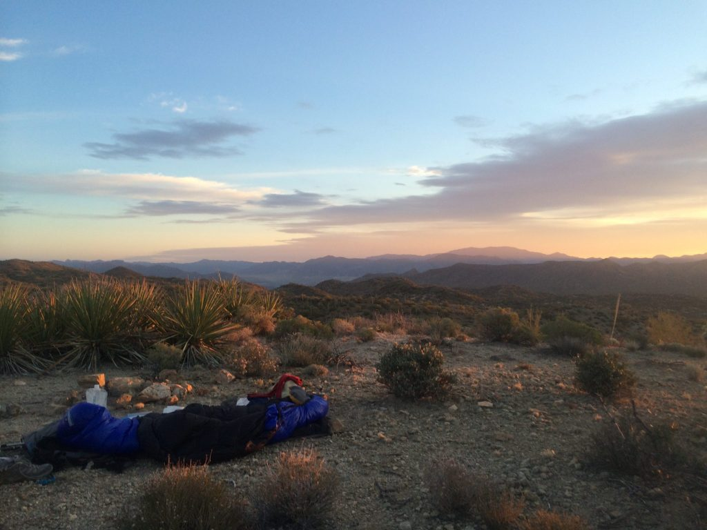 Sleeping bag and hiking gear laid out in the desert