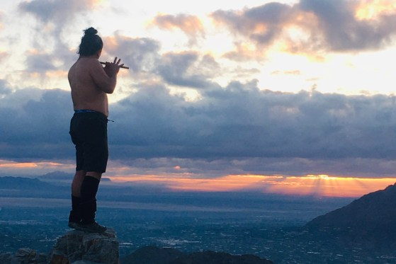 man playing flute on mountain top