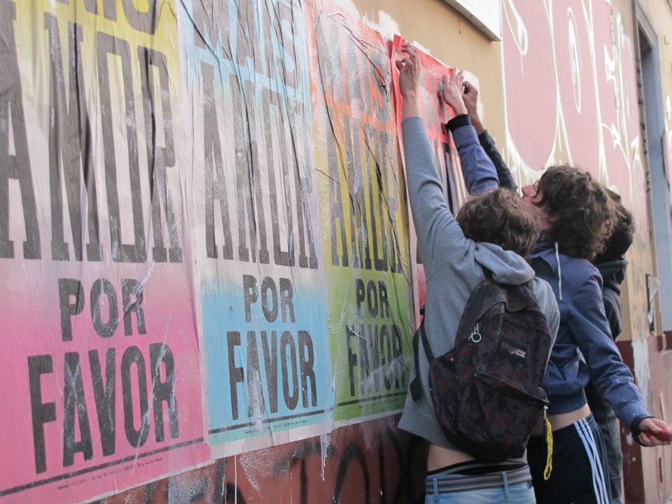 Chicos pegando pósters de Mais amor por favor en las calles de Buenos Aires. Foto