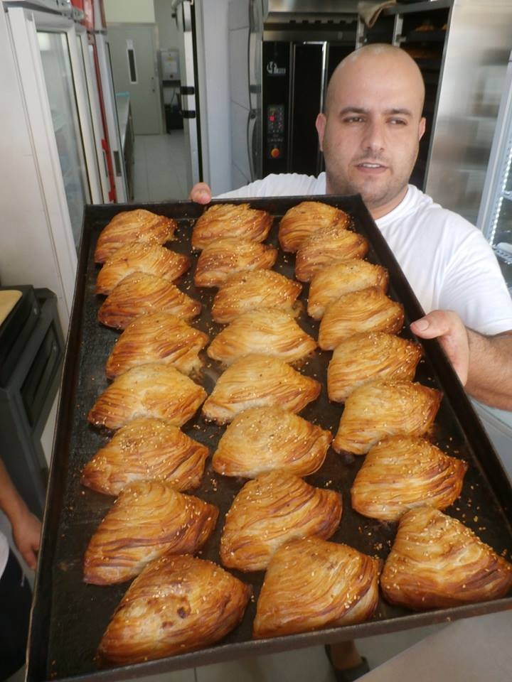 A Maltese 'pastizzi' baker, savoury, baked flaked pastry sleeves filled with mashed peas and onions or rikotta.