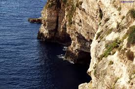 -The-blue-Mediterranean-Sea-with-Ghar-Hassan-cave-set-in-the-sheer-cliff
