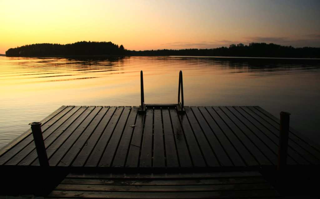 Wooden jetty steps into lake at post sunset Finland