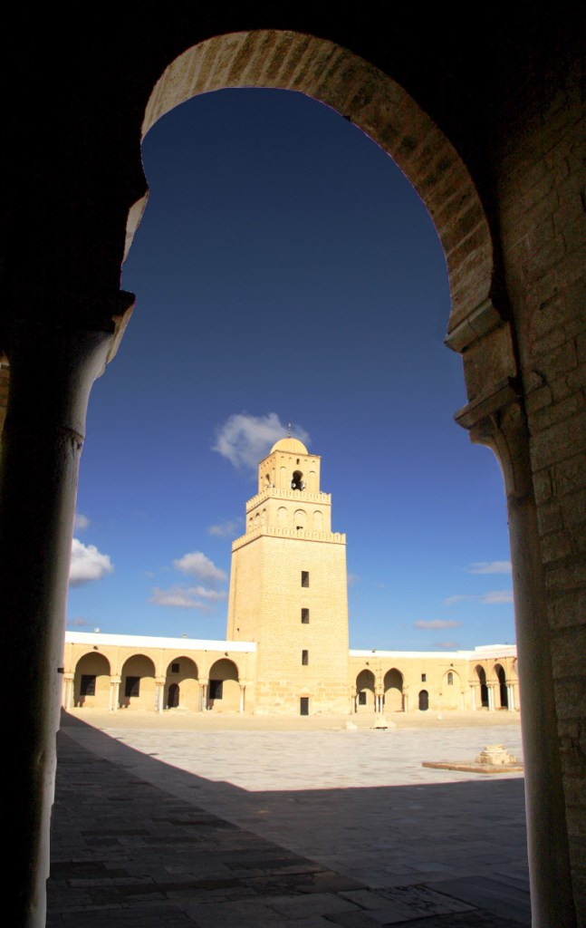 Minaret framed by arches and pillars of the courtyard Oqba Masjid Kairouan Tunisia