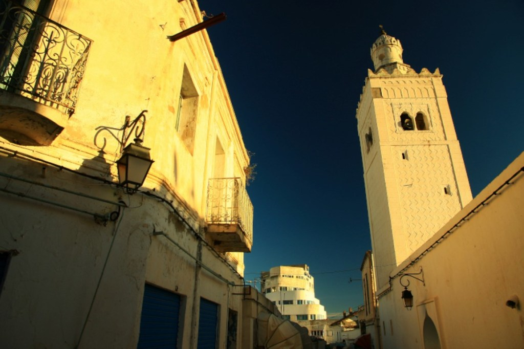Minaret and apartments bathed in evening light El Kef
