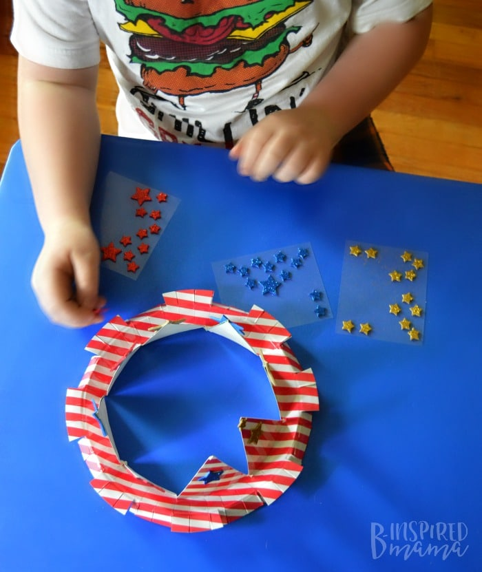 An Easy 4th of July Craft for Kids - A Stars and Stripes Crown - Sawyer adding the star stickers - at B-Inspired Mama