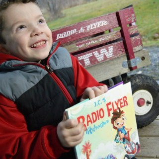 JC surprised to see his name on his My Radio Flyer Adventure Book - at B-Inspired Mama
