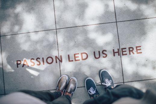 """Der Fotograf hält den Fotoaparat in Brusthöhe und fotografiert seine Beine und Füße sowie die von einer Person, die neben ihm steht. Man sieht als stehlenhaft die Beine und Schuh sowie auf dem Bode eine englische Aufschrift die lautet """"Passion led uns here""""."""