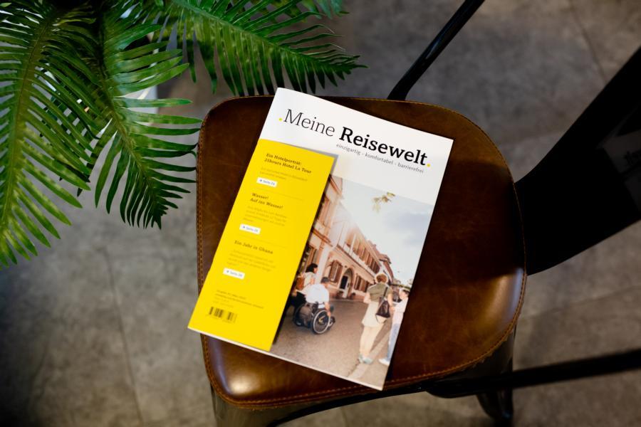 """Das Reisemagazin """"Meine Reisewelt einzigartig - komfortabel - barrierefrei"""" ist auf einem dunkeln, edelausstehenden Stuhl positioniert."""
