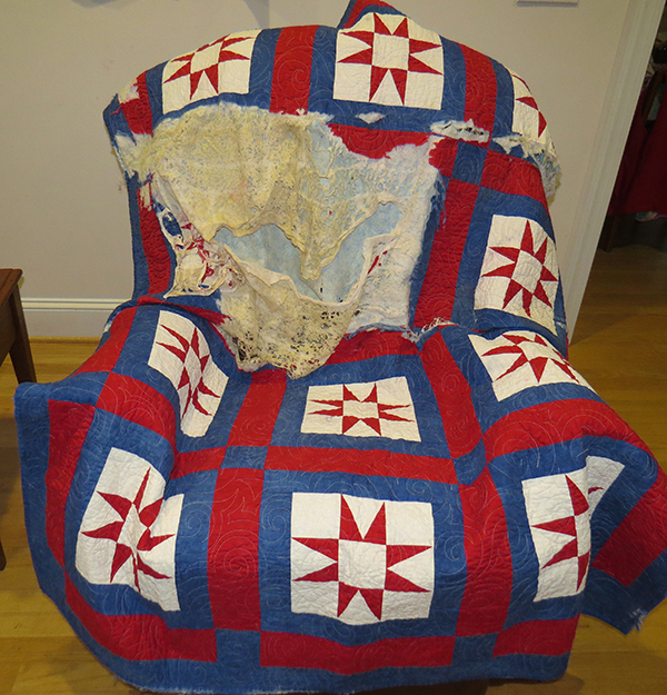 Full view of quilt damaged by fire.