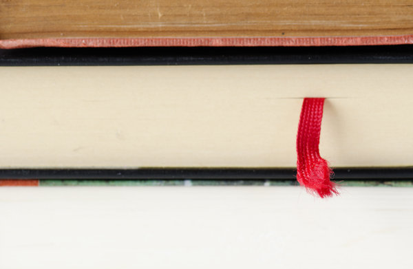 Book mark: red bookmark in a pile of books