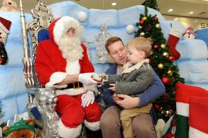 Youngsters queued to meet Santa when he opened the doors of his igloo at Northfield Shopping Centre. The busy shopping centre has been transformed into the North Pole, with animated winter wildlife and Eskimos helping Santa to greet children Santa with Arthur Caning (2) from Northfield and Arthur's dad, Jamie Canning.