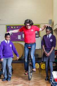 Emani (left) and Tatyan (right) help The Fool Monty Jester to ride his unicycle