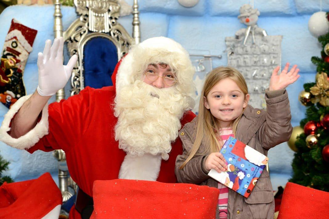 Santa greets a local youngster at his igloo grotto at Northfield Shopping Centre