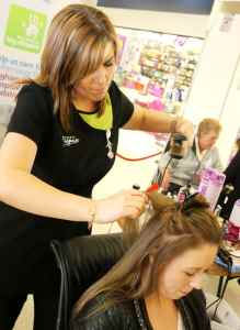 Student Sam Richards straightens the hair of Robyn Hollier from Selly Oak