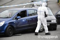 Forensic officers examine the vehicles