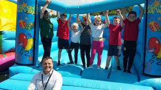 Pupils help ISG site manager Alun Roberts and Morrisons Rubery Community Champion Jane Williams test out the inflatables