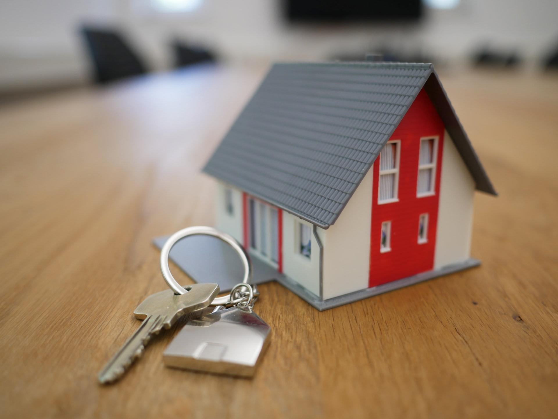 Macheta unei case asezata pe o masa, iar langa aceasta se afla cheia de la intrare, in marime naturala