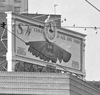 Billboard of S&W produce, an early food brand. A clock is in the top middle. In later years passenger rail lines and other advertisers continued to show a clock.