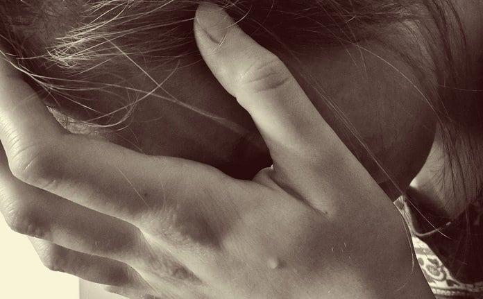 fiatal nő kezébe temeti az arcát