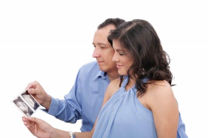 szülő pár ultrahang felvételt néznek együtt