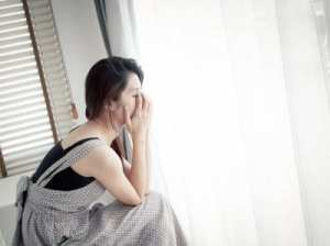 fiatal szomorú nő ül az ablaknál