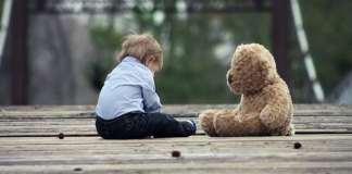 kisfiú ül a földön egy plüssmackó mellett