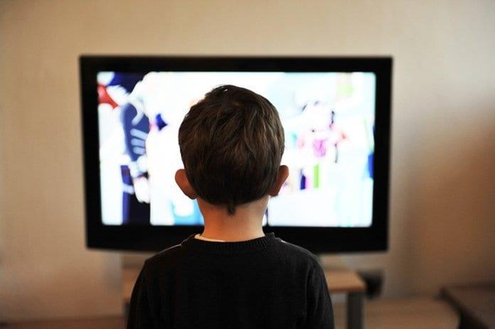 gyerek ül a tévé előtt