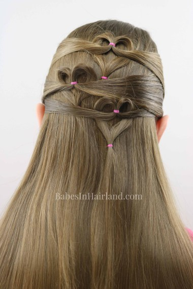 Need a cute Valentine's Day heart hairstyle but don't have much time? Try this quick and easy triple heart pullback hairstyle from BabesInHairland. Love is in the hair with this cute Valentine's Day hairstyle. #hair #valentinesday #hearthair #hearts #loveisinthehair