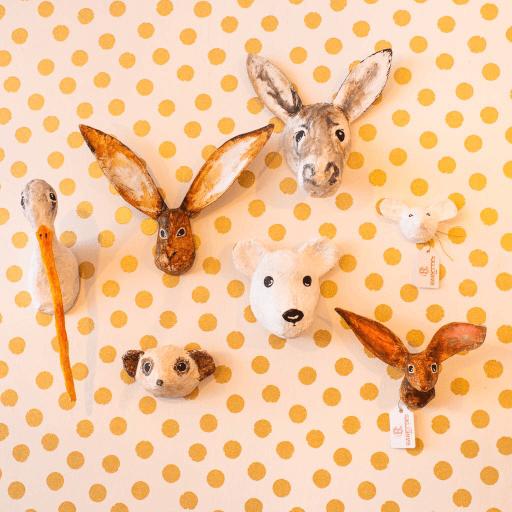 leuke muur vol met papiermache dierenkoppen je ziet hier een ooievaar haas ezel muis stokstaartje en een ijsbeer